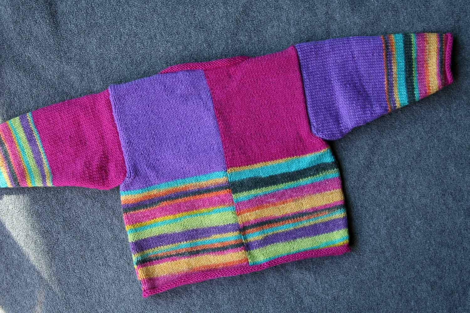 Back of Lucy cardigan with intarsia blocks of colour and self-patterning yarn.