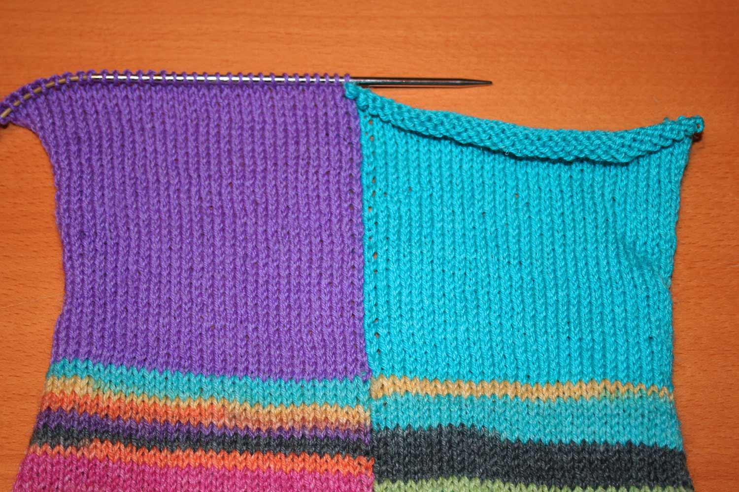 Intarsia project with the purple half on the needle and the turquoise half with needle removed.