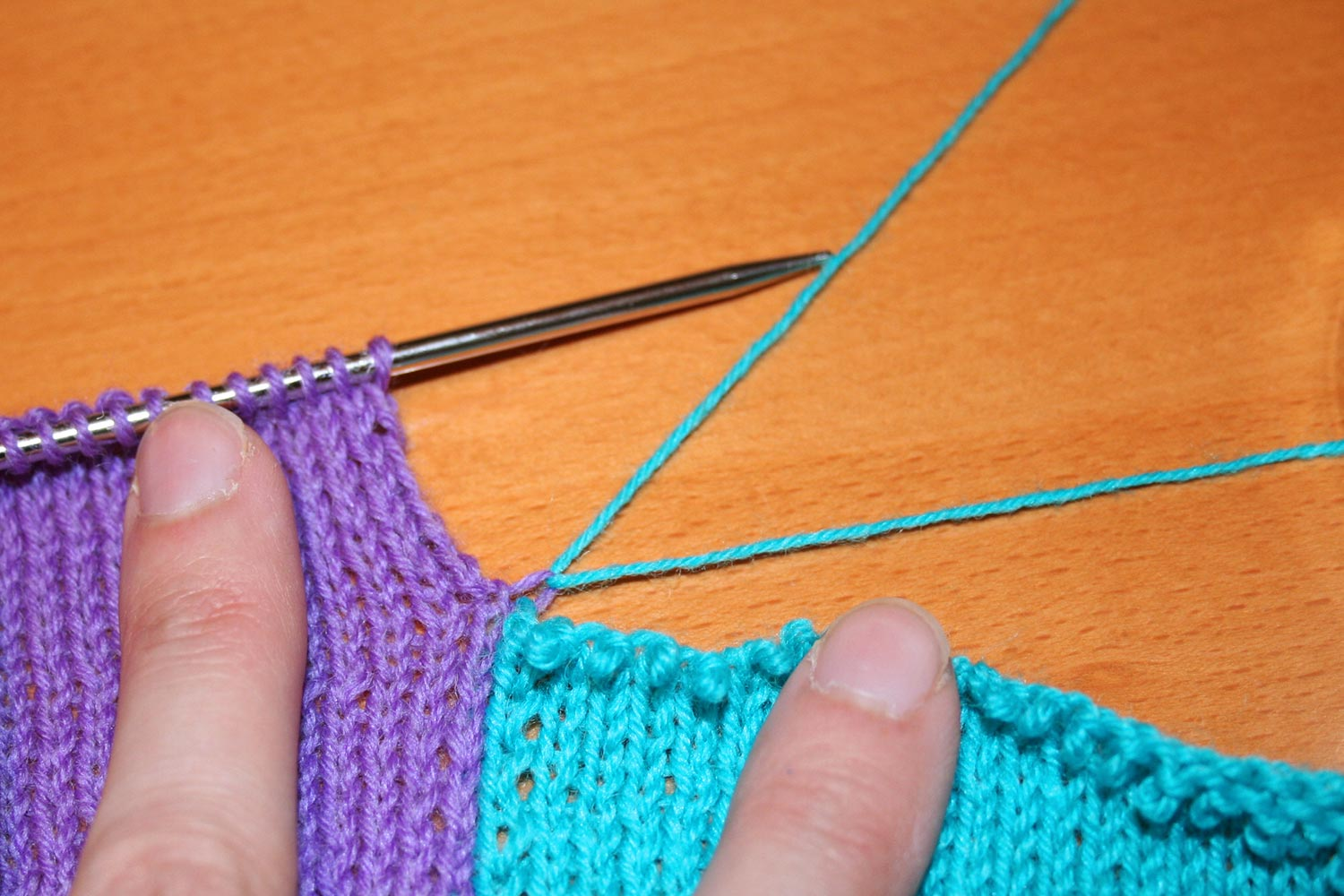 Ripping back the turquoise colour block while the purple block remains on the knitting needle. Yarn pulled taught to show where it joins to purple block.