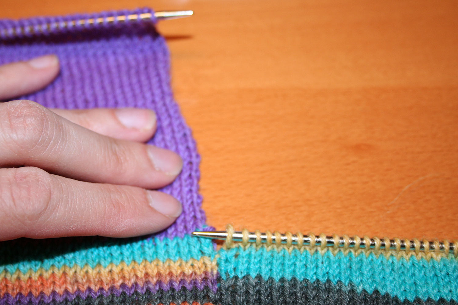 Intarsia project with large colour block removed and knitting needles on two different rows several inches apart.