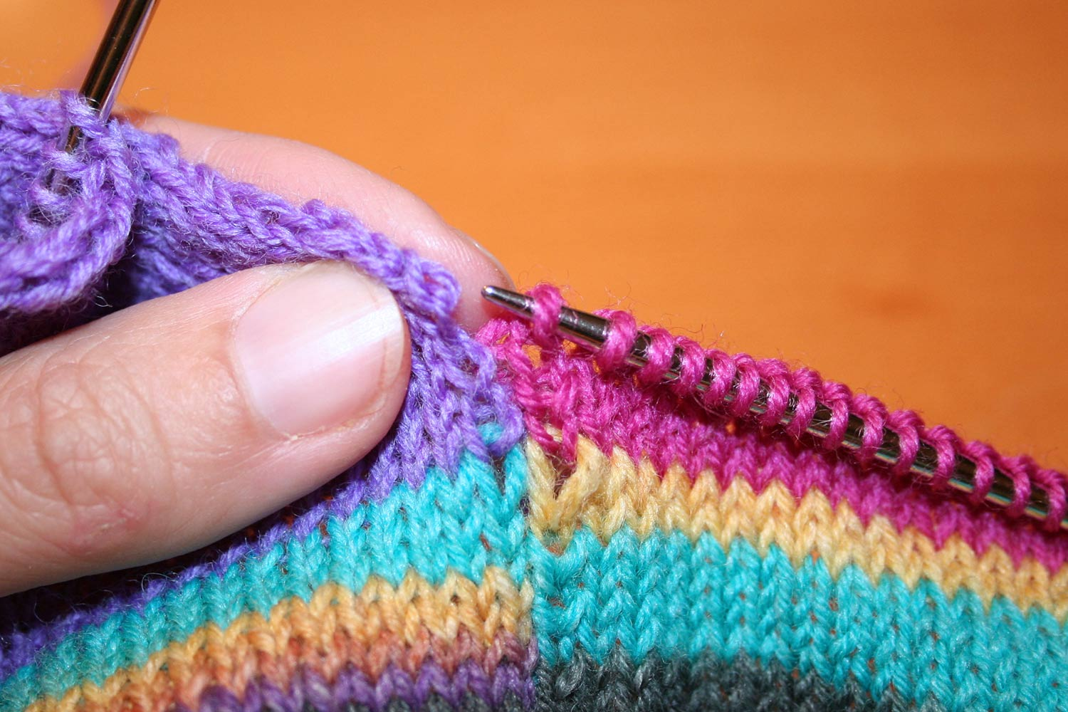 Reworking and intarsia colour block with right needle pointing towards selvedge loop where it will be joined.