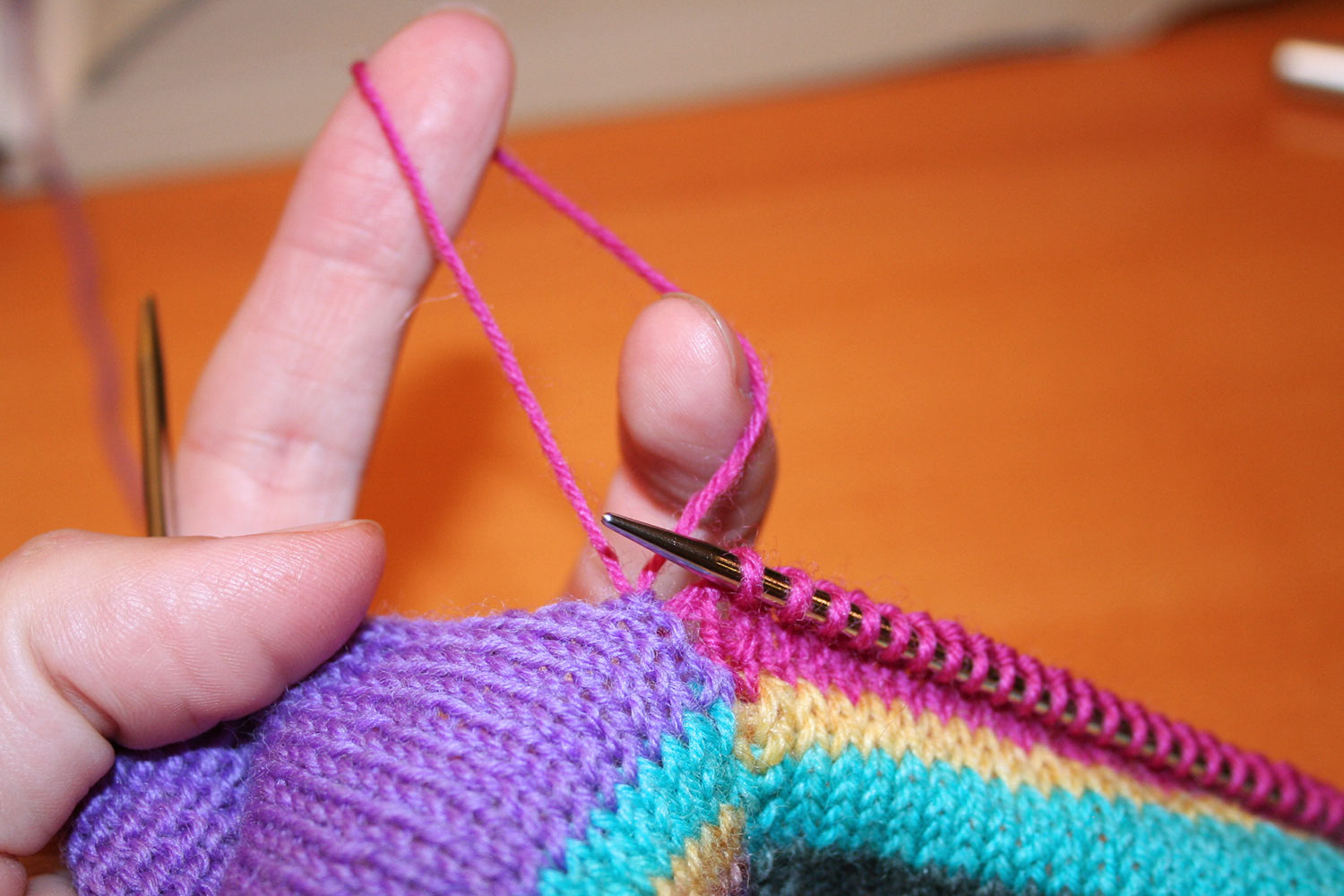 Fingers enlarging a stitch so it's becoming a large loop of yarn.