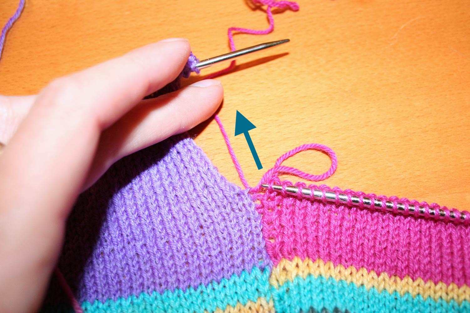 With right side showing, right side row is complete and an arrow indicates the direction to pull the yarn to tighten up the slack on the large loop.
