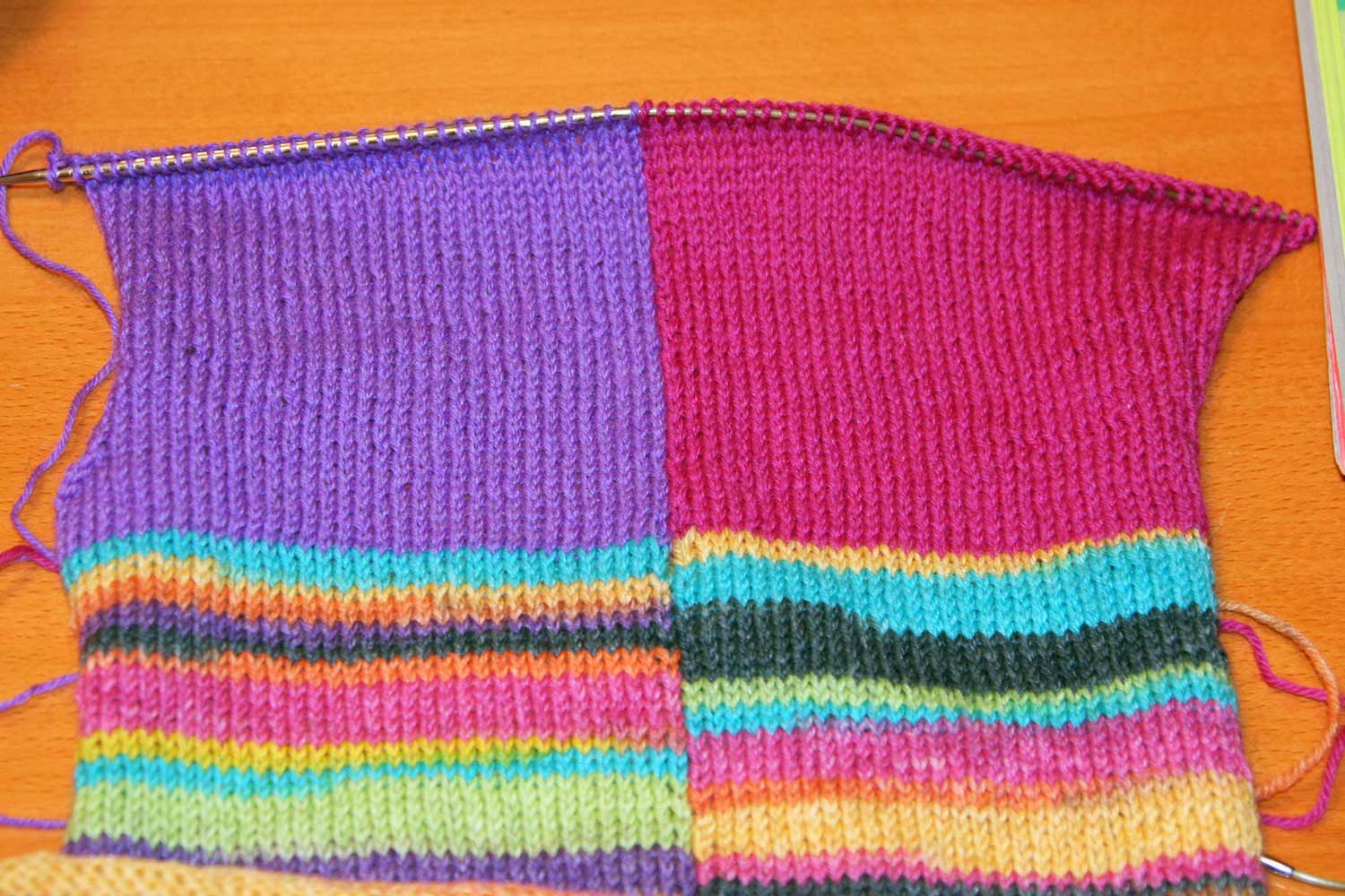 Intarsia project on the needles showing that the colour block on the right has been replaced with pink yarn.