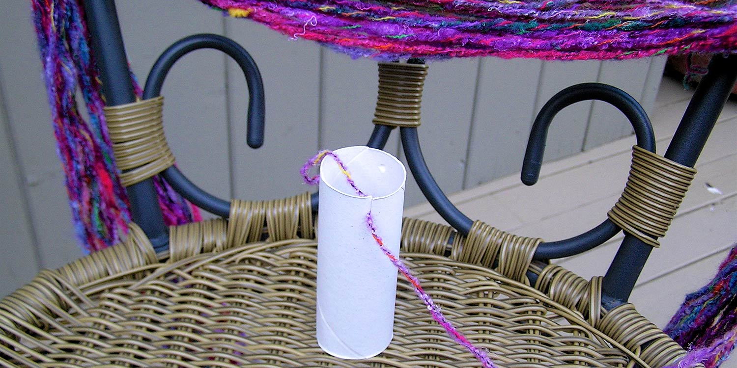 Toilet paper tube with a slit cut in it and a strand of yarn; part of the skein can also be seen draped on a chair.