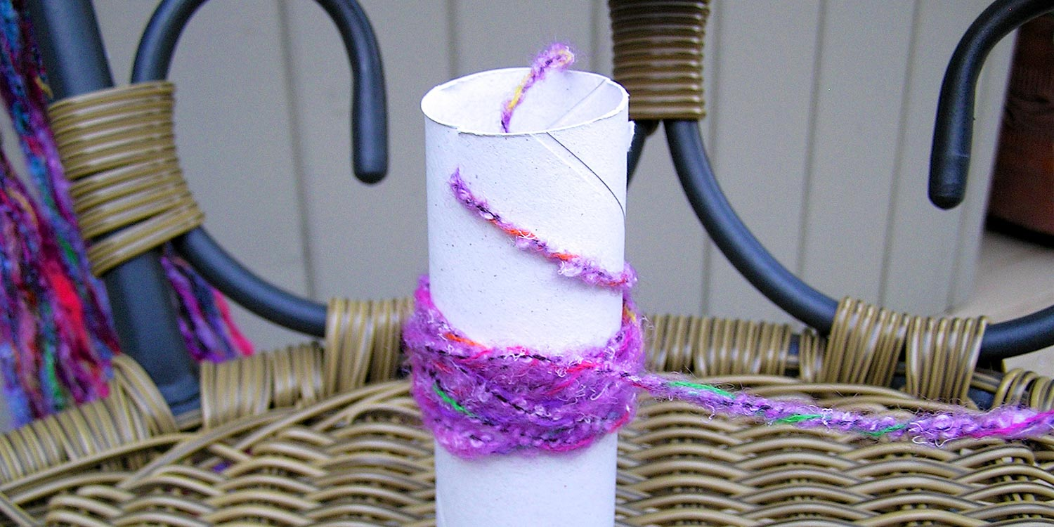 Toilet paper tube with a small amount of yarn wrapped around it.