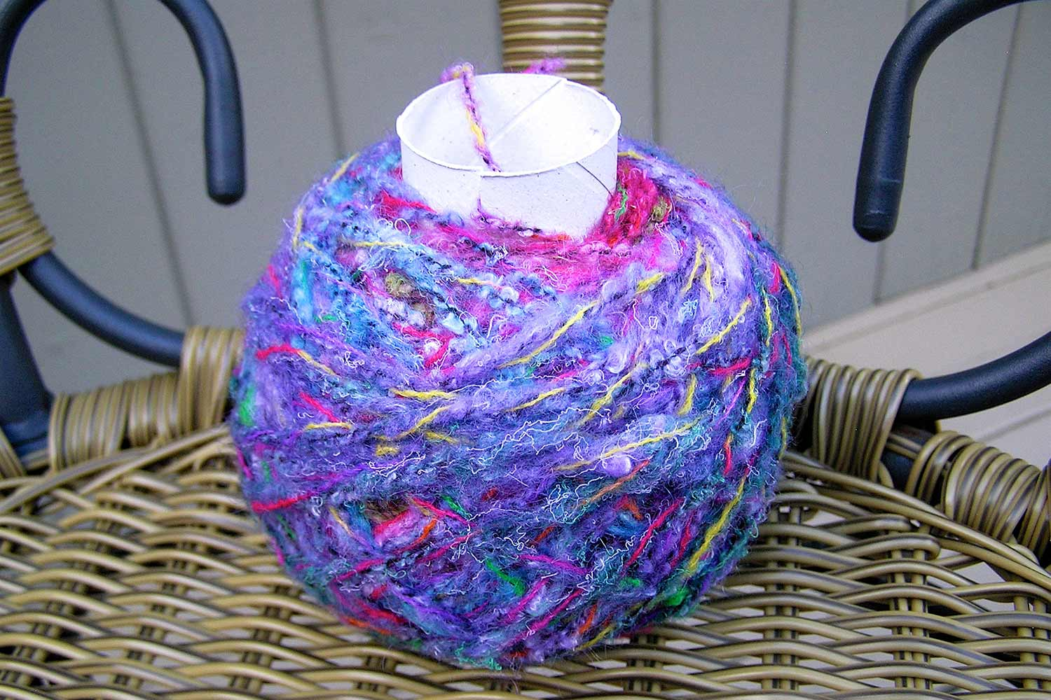 Toilet paper tube with a full skein of yarn wrapped around it looking very much like a ball of yarn.