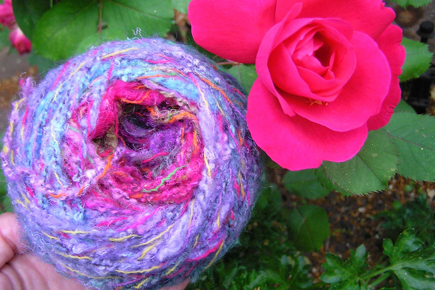Very colourful hand wound ball of yarn being held beside a bright pink/red flower in the garden.