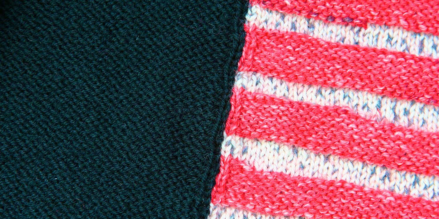 A black reverse stocking stitch piece of knitted fabric has been seamed to a red and white striped piece; a column of knit stitches can be seen along each side of the seam.