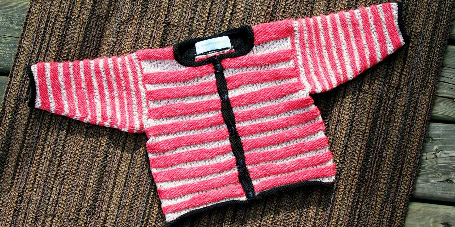 Red and white striped baby sweater with black edging is laying flat on a carpet.