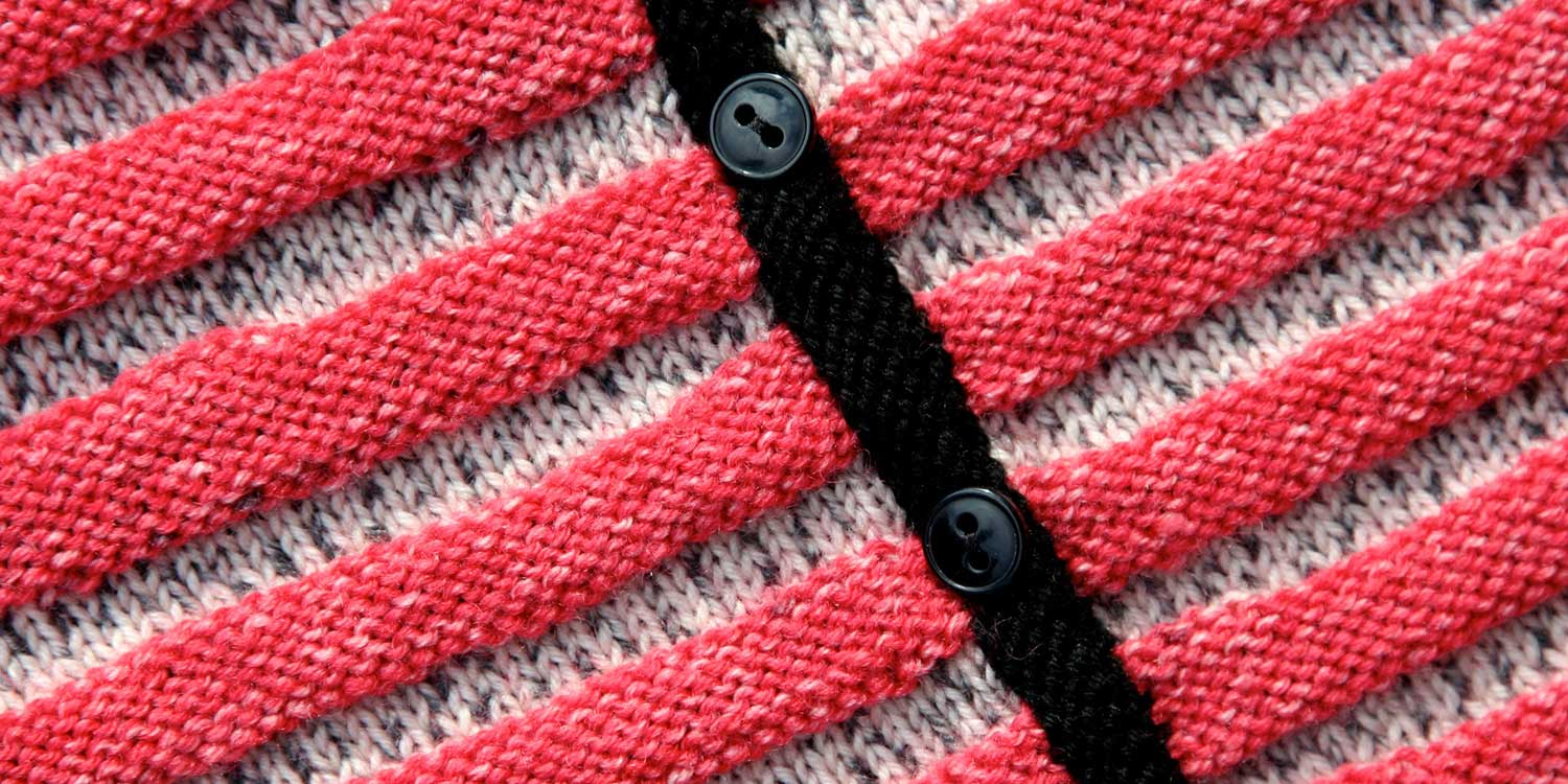Tight shot of the black button bands on a textured red and white baby cardigan.