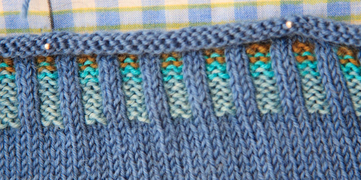 Closeup of corrugated ribbing in blues and gold with pins in it.
