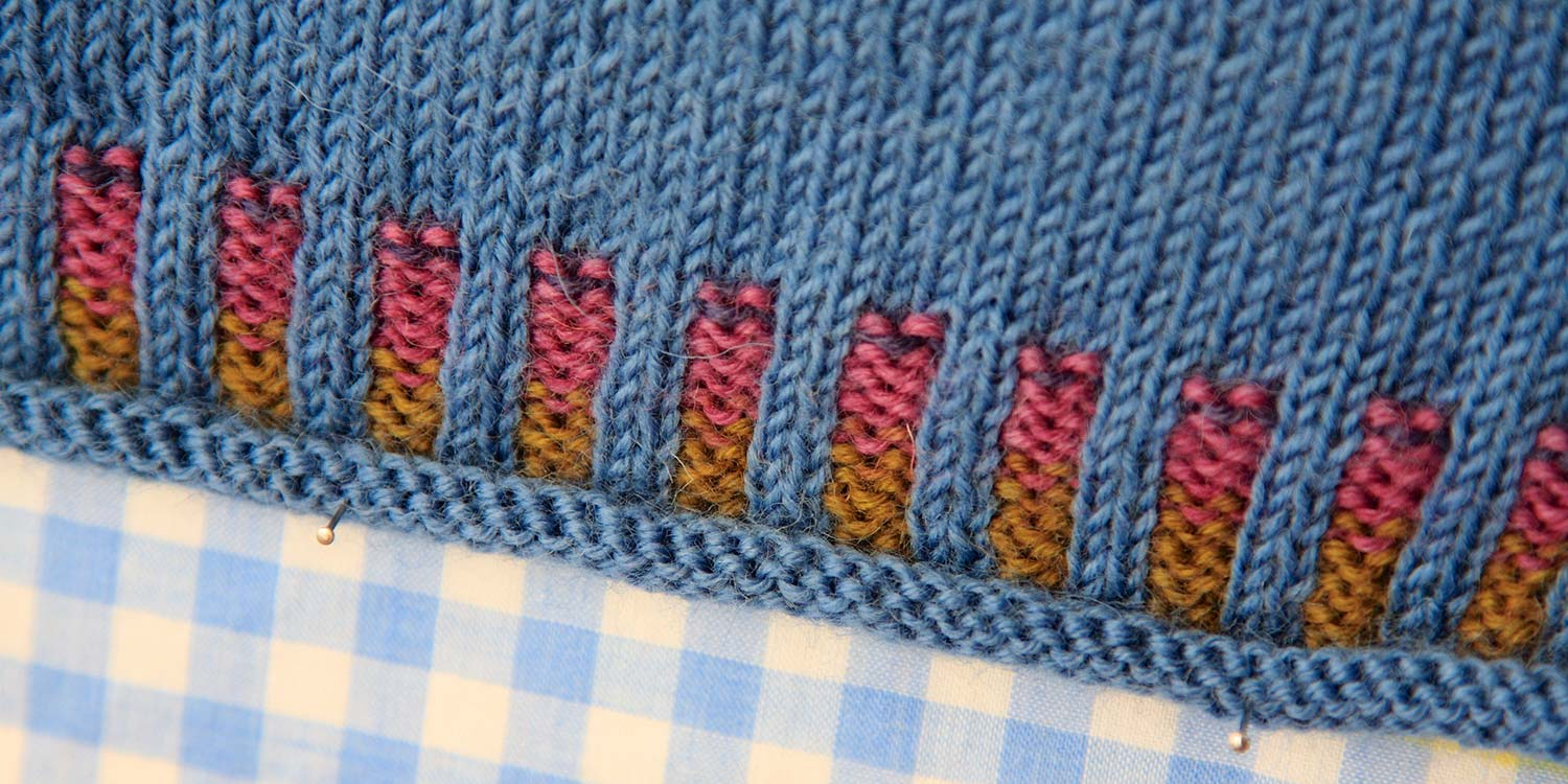 Closeup of corrugated ribbing in blues, pink and gold with pins in it and sitting on gingham fabric.
