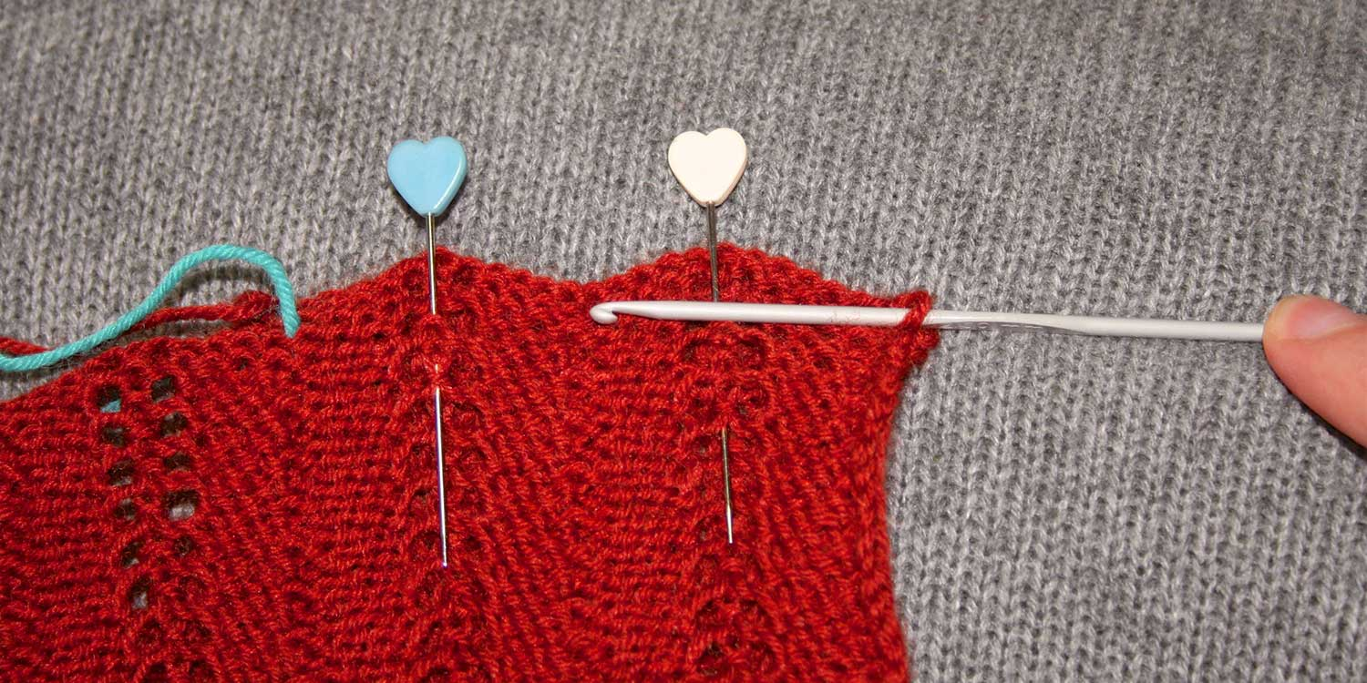 Wrong side of knitting showing with two pins; the bind-off edge is scalloped; a crochet hook has one stitch on it and is held horizontal, drawing a line across the knitting showing where to stitch a straight line.