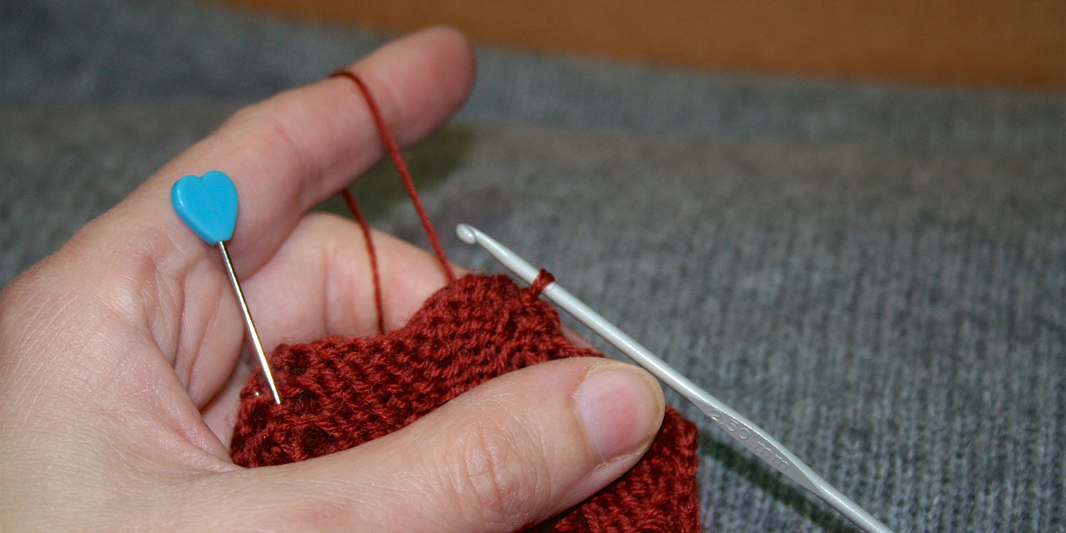 Left hand holding knitting and tensioning yarn for crochet hook that's being used for seam.