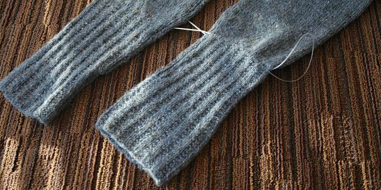 Two sleeve cuffs, one of which is oddly shaped and has a circular needle threaded through all the stitches just above the ribbing.
