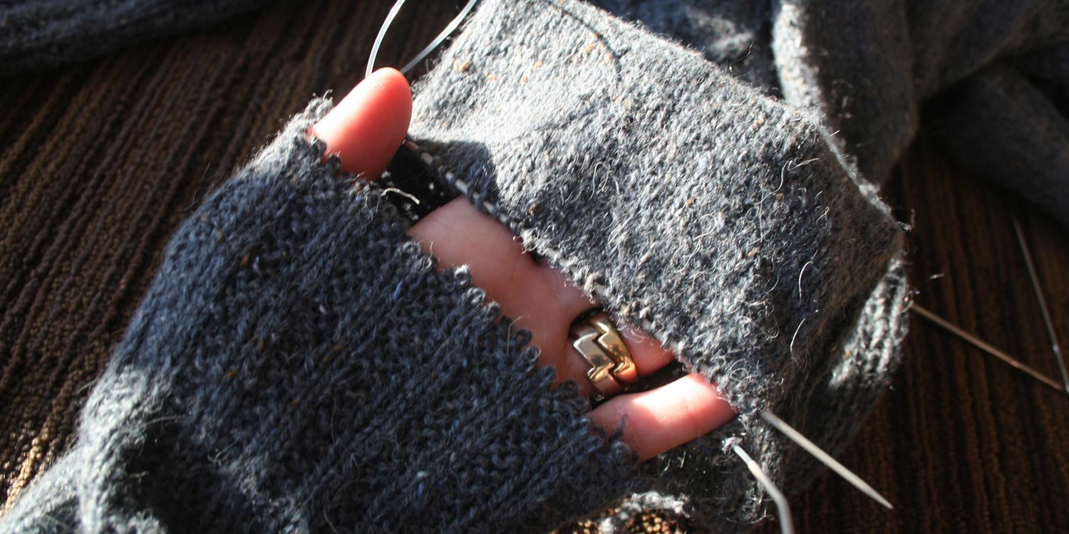 Hand slipped into a sweater cuff that's been separated from the rest of the sleeve; stitches on sleeve are safe on a circular needle.