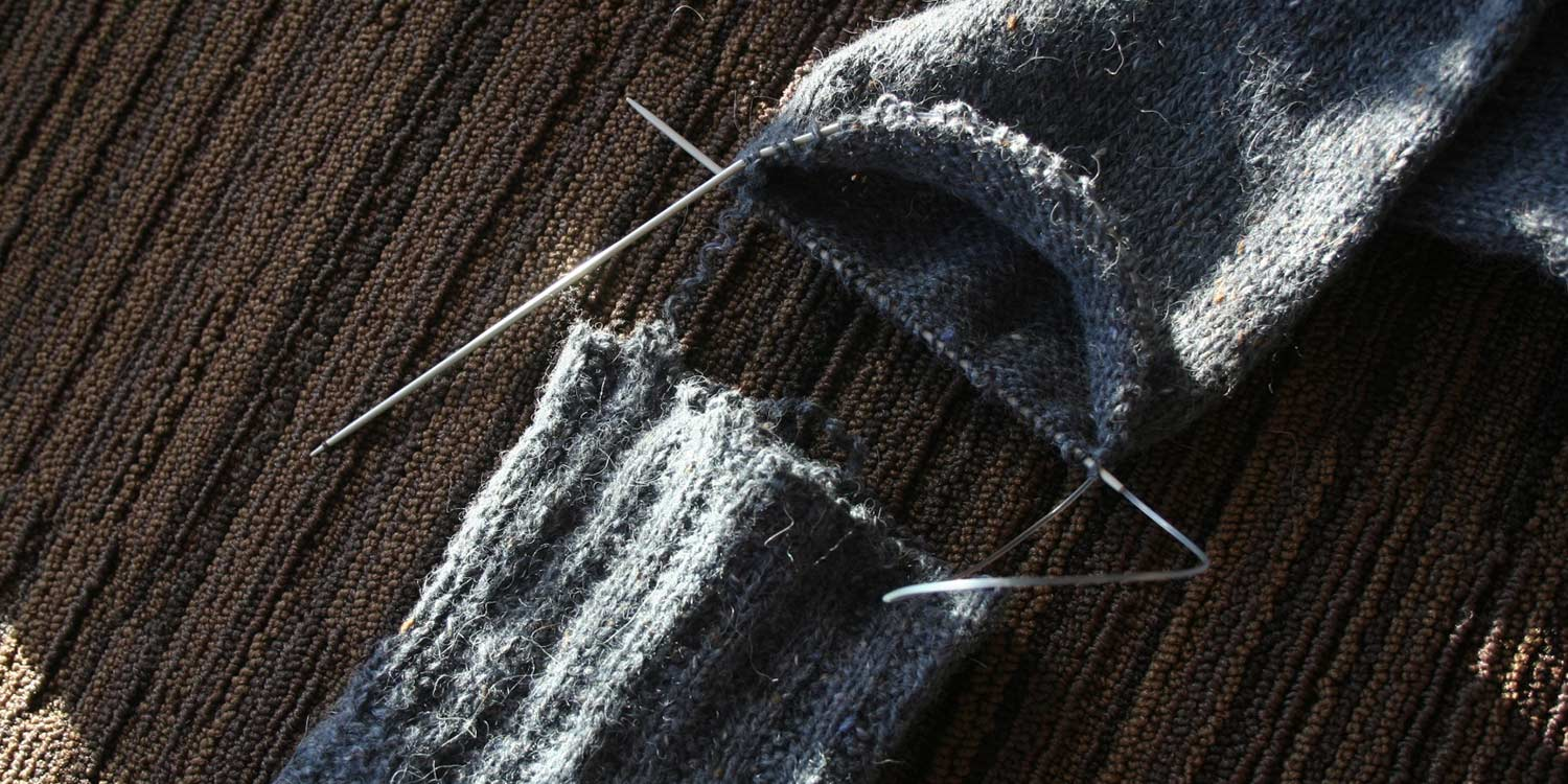Sweater sleeve on a circular needle with the separated sleeve cuff sitting next to it.