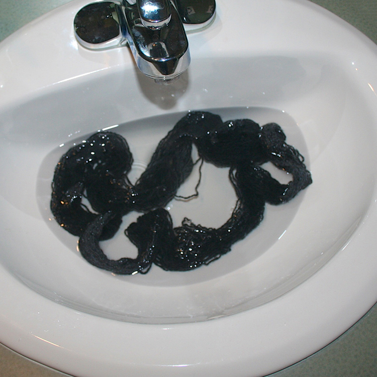 A small skein of yarn in a bathroom sink full of water.