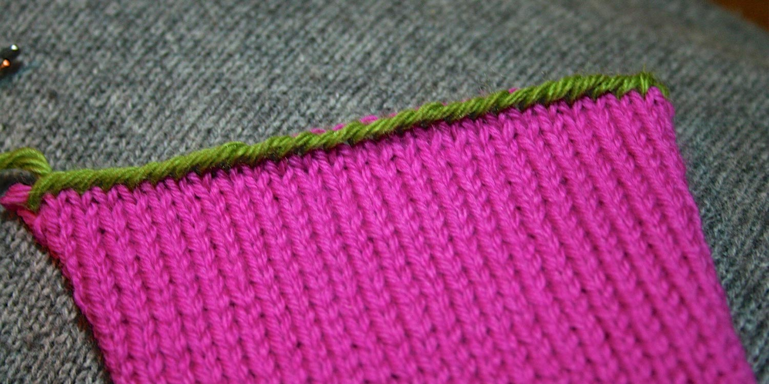 Pink knitting with a green bound off edge that looks like a line of overlapping slanted stitches