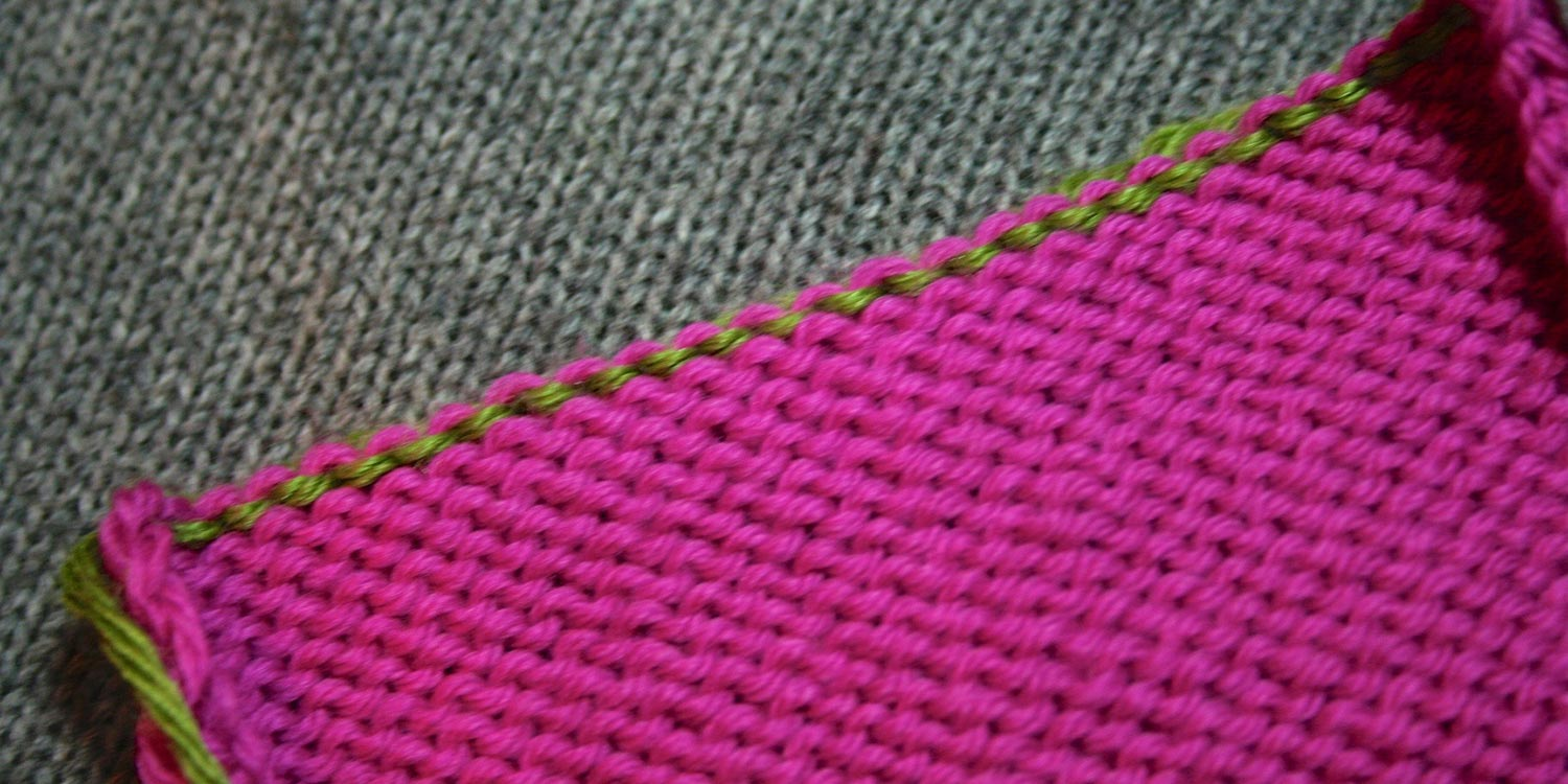 Wrong side of pink knitting showing what looks like green purl bumps at top edge.