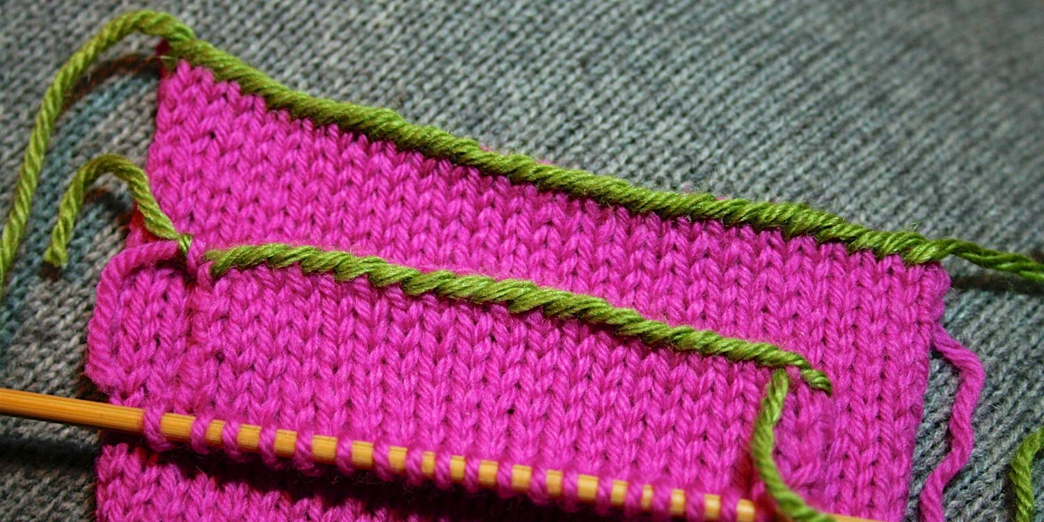 Two swatches one on top of another both showing identical edges with contrasting yarn; top swatch is clearly a cast-on edge while bottom swatch was worked as a bind off.
