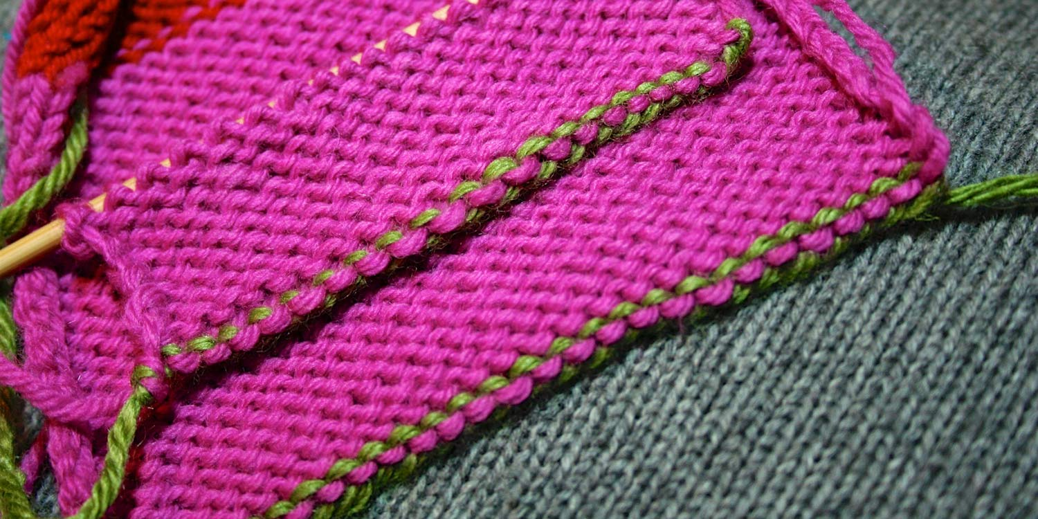 Wrong side of two swatches lying on top of one another showing the same edging; the top one worked as a cast on and the other a bind off.