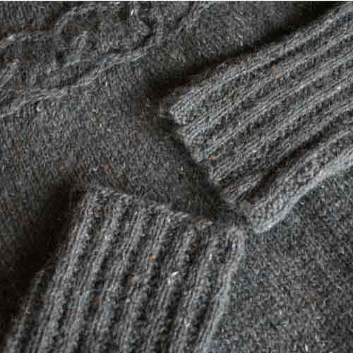 Cuffs of two sleeves laying on top of sweater so both edges can be compared; they both look the same.