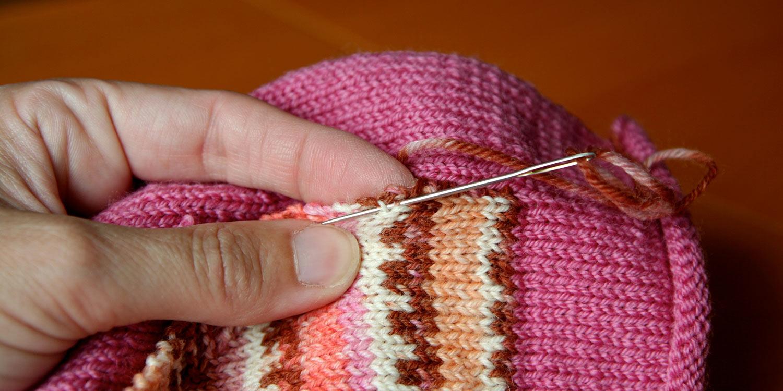 Threaded needle inserted under two bars on selvedge edge of pocket.