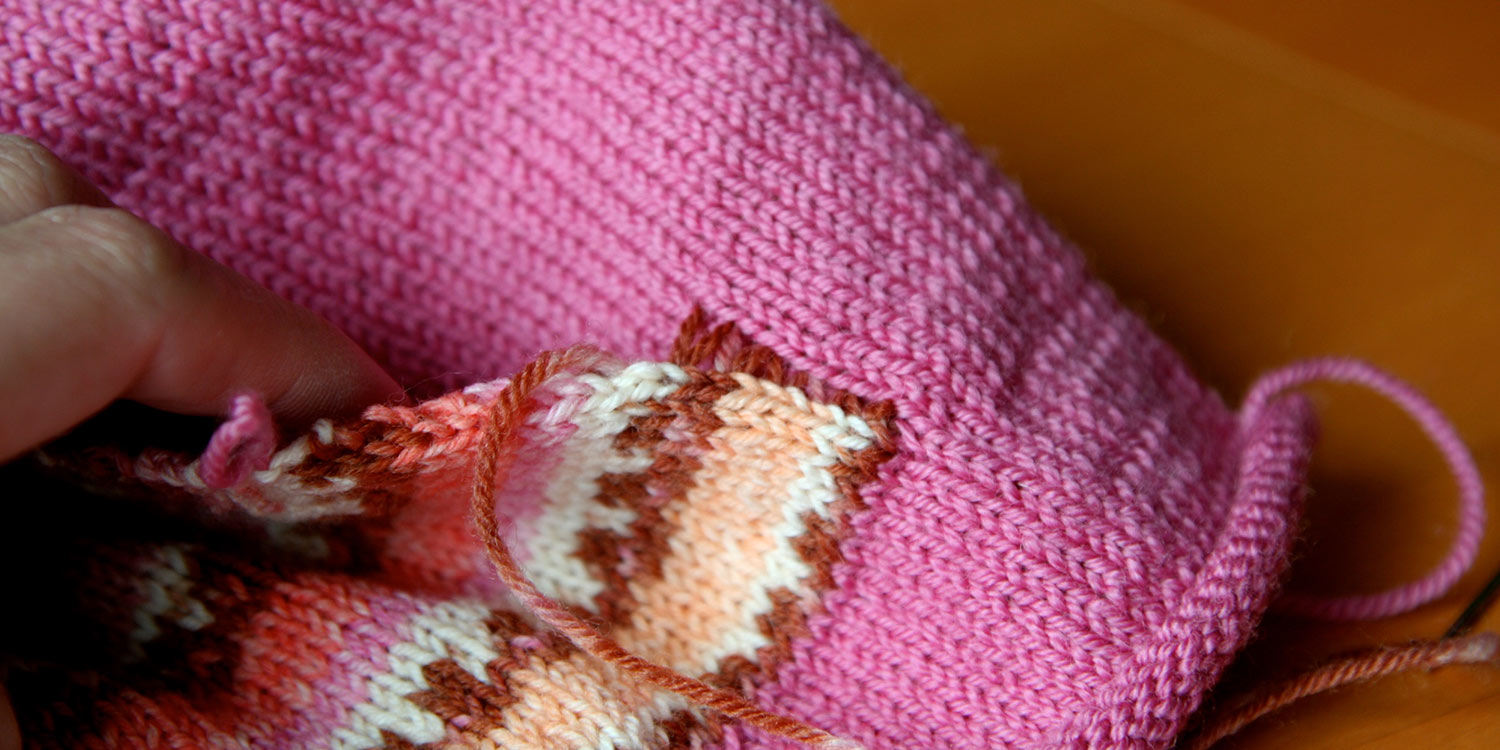 Loosely seamed pocket edge showing where stitches were made in sweater front and pocket edge.