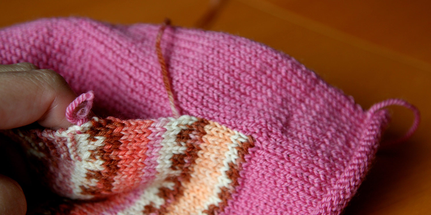 Tail of yarn extending from partially seamed pocket edge and a neat and tidy seam.