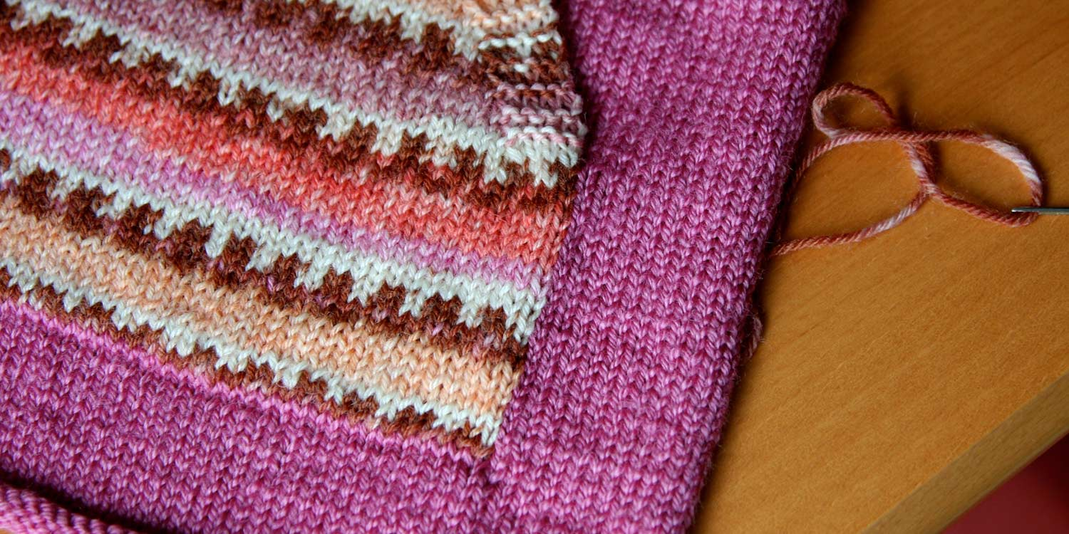Pocket knit in self-patterning yarn that's been sewn to solid-coloured sweater front.