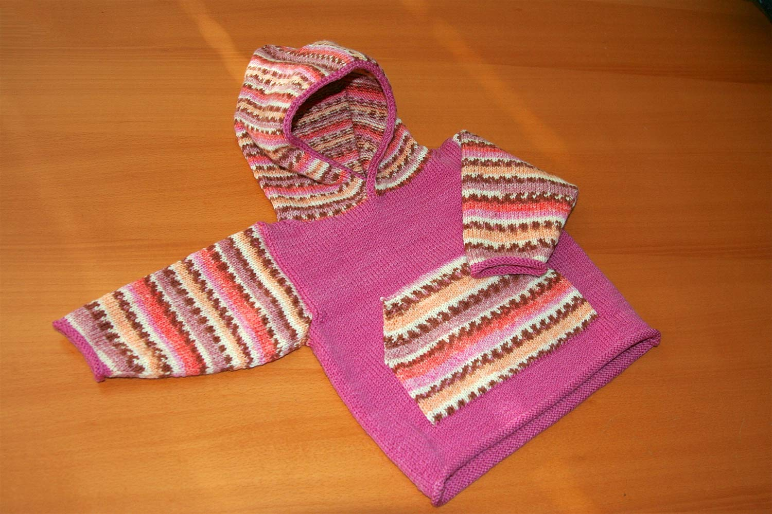 Baby hoodie lying flat on wood table with one arm straight out from body and other folded onto front; pink body with sleeves, pocket and hood worked in self-patterning yarn.