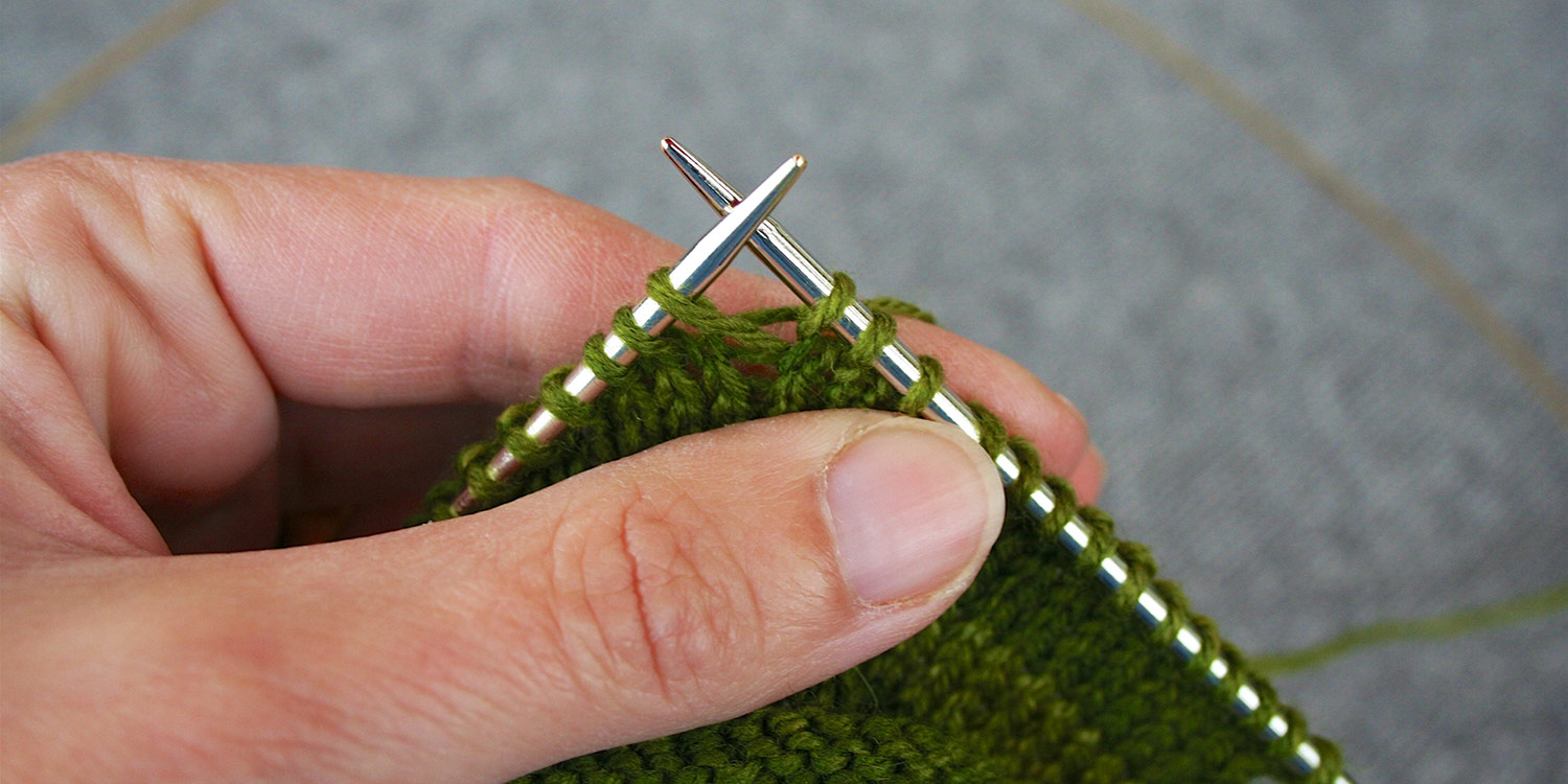 Left hand holds knitting up, showing completed right-leaning raised increase.