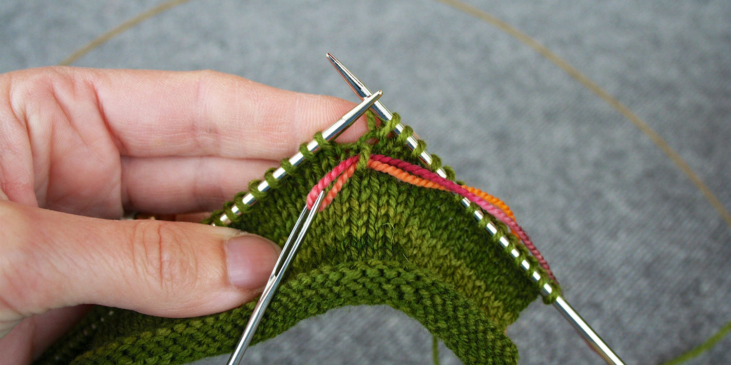 Tapestry needle is hanging from contrasting yarn that's threaded through a stitch two rows below last stitch worked on right needle.