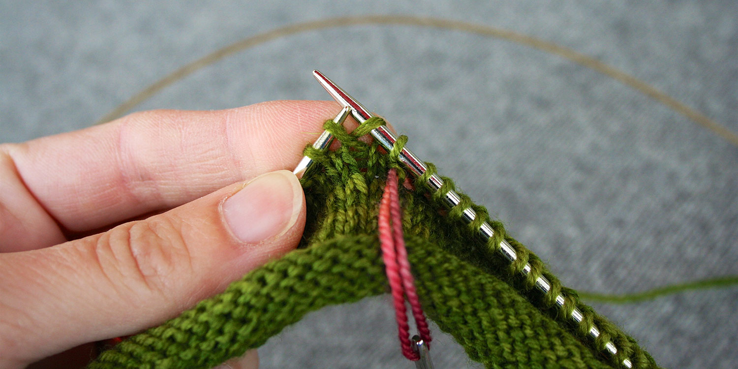 Right needle is inserted into stitch one row immediately below next stitch on left needle, while tapestry needle is hanging from a contrasting coloured length of yarn.