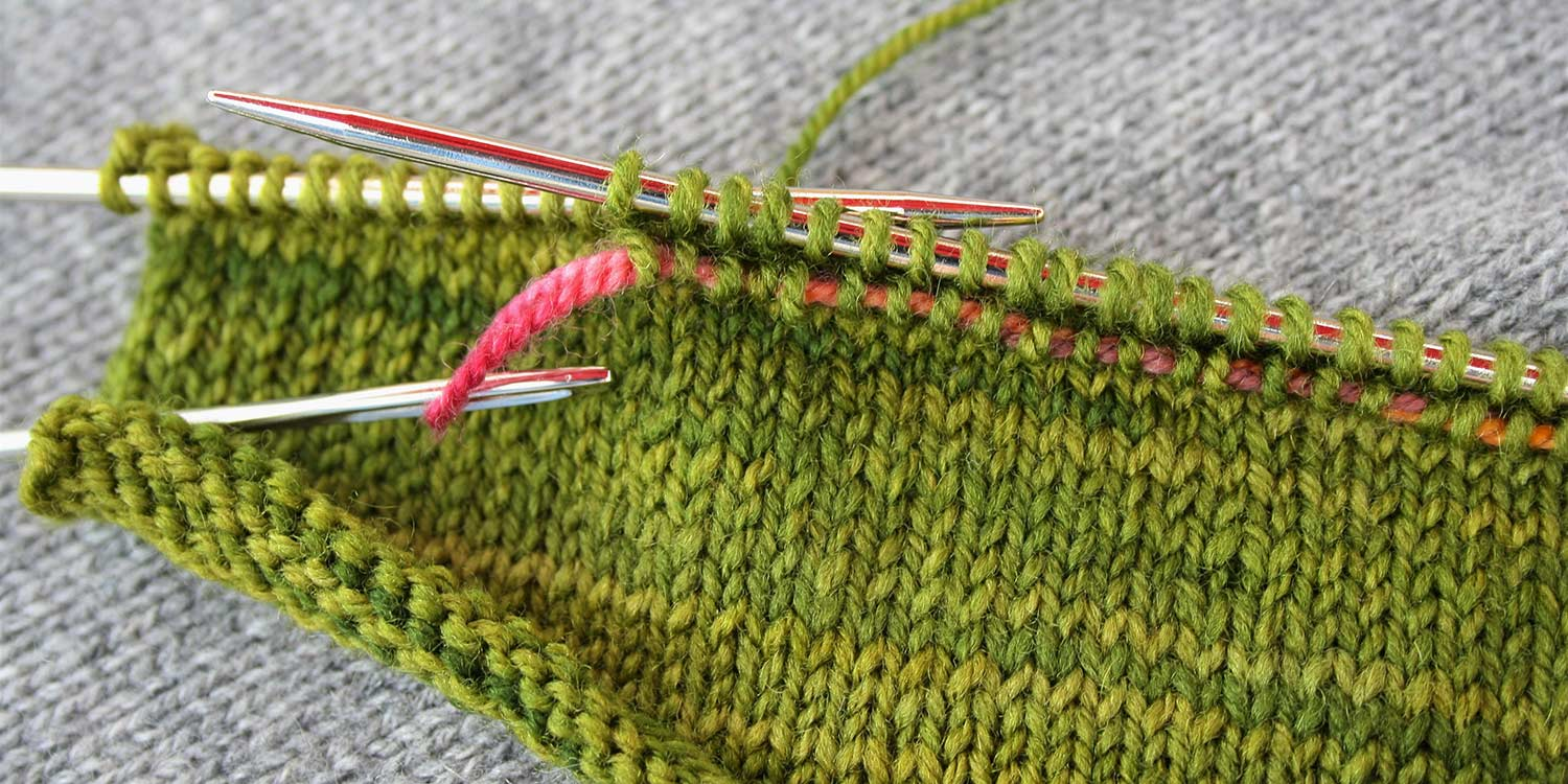 A length of contrasting yarn threaded through stitches in row immediately below all the stitches on right needle; several stitches on left needle still to be worked.