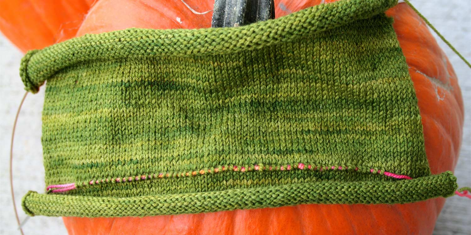 Several inches of stocking stitch knitting on the needles with a length of contrasting yarn threaded through the majority of the stitches in a row closer to the cast on edge.