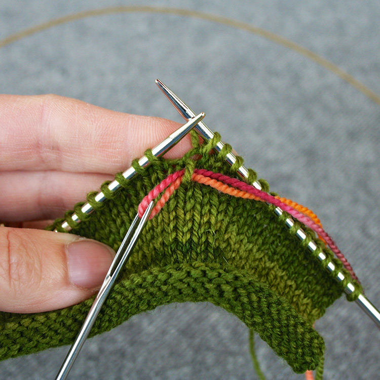 Contrasting yarn threaded through a stitch in a row below stitches on the needle, reserving the first stitch to be used in the kangaroo pocket.