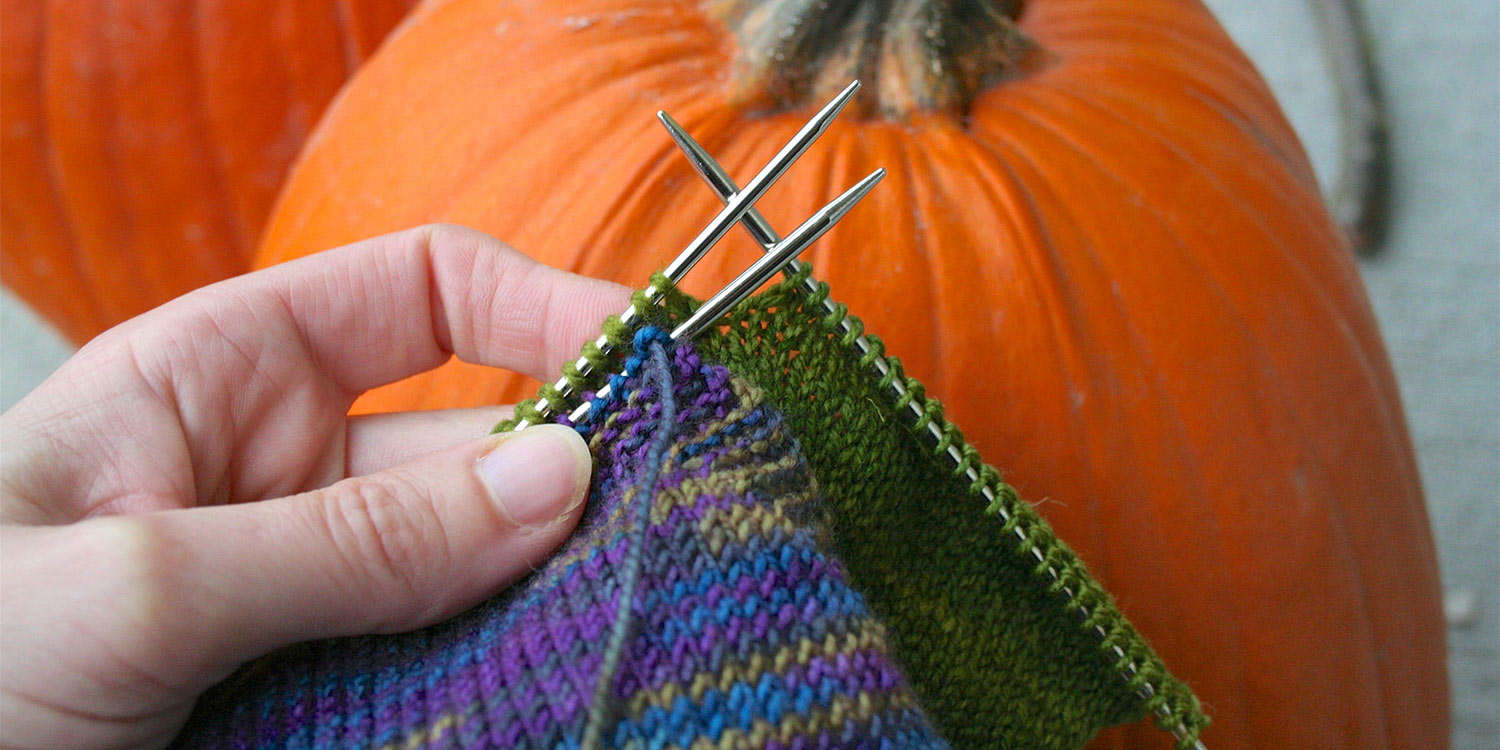 Partial row of sweater front is worked and the pocket is completed on a separate needle held in front of the sweater, both with right sides facing and needles held parallel in left hand.