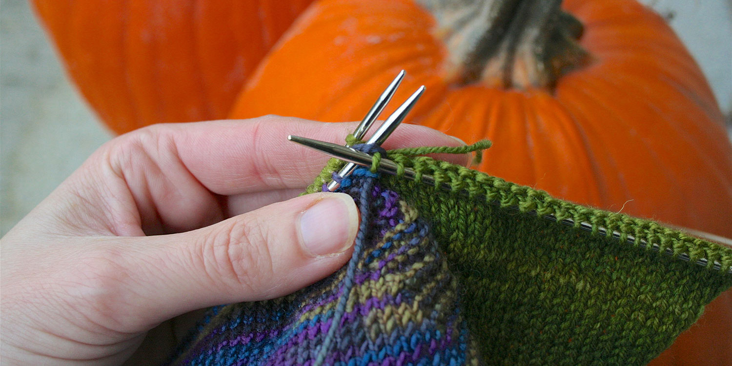 Left hand holds two needles with stitches, held parallel; right needle is drawing a knit stitch through the first stitch on both needles, similar to a knit two together.