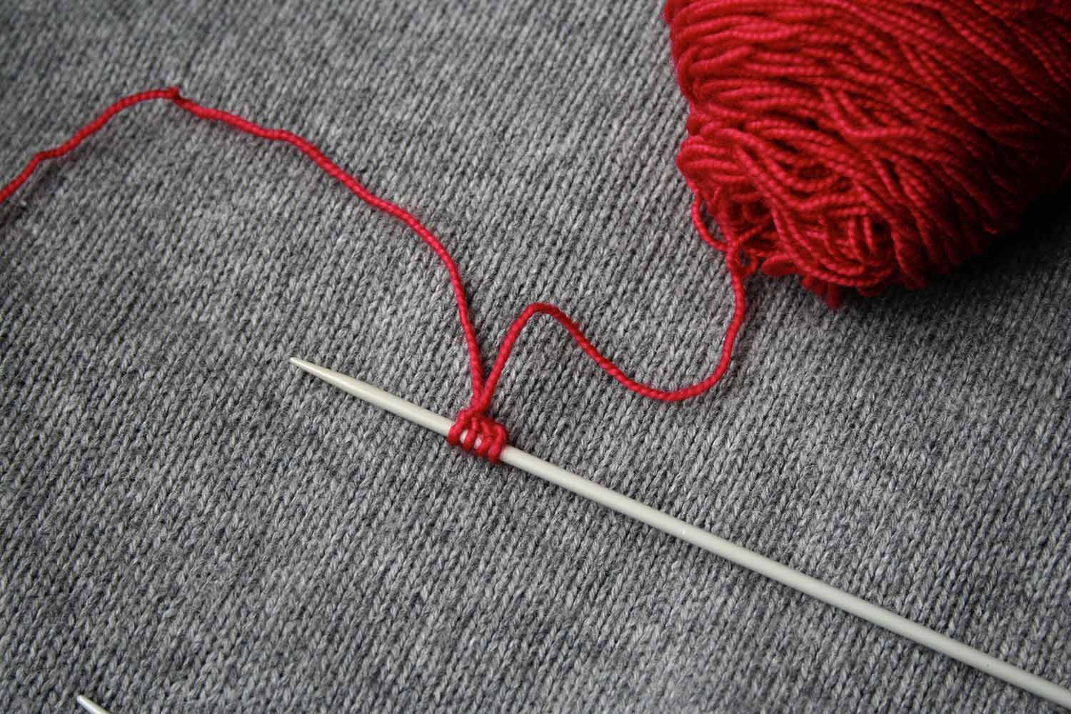 Double pointed needle resting on a knitted surface with four stitches cast on and a ball of red yarn.
