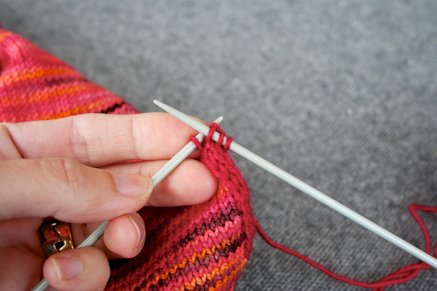 Three stitches on right needle and fourth stitch on left needle; below needles the applied i-cord can be seen along the edge of a piece of knitting.