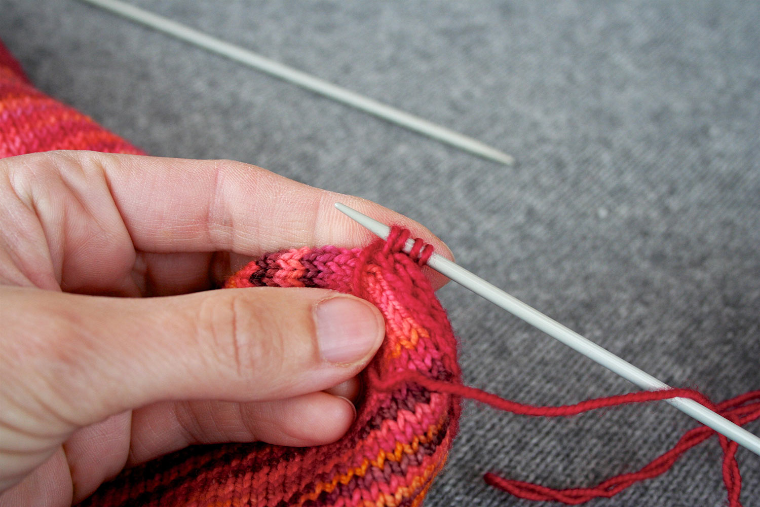 Four stitches on right needle with yarn brought to front and held in place by thumb of left hand; empty needle out of focus in background.
