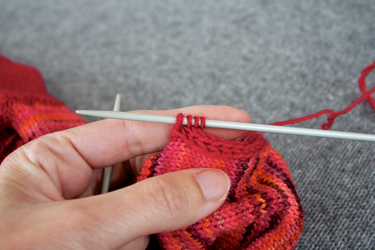 Left hand holding up knitting and showing four stitches on right needle.