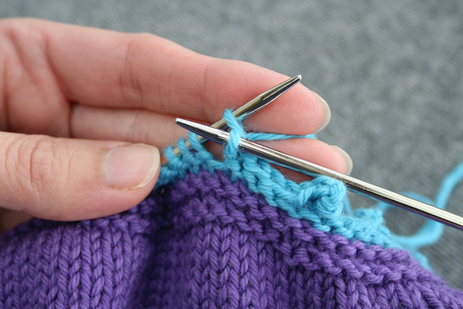 Right needle drawing a stitch through to the front from between first and second stitch on left needle.
