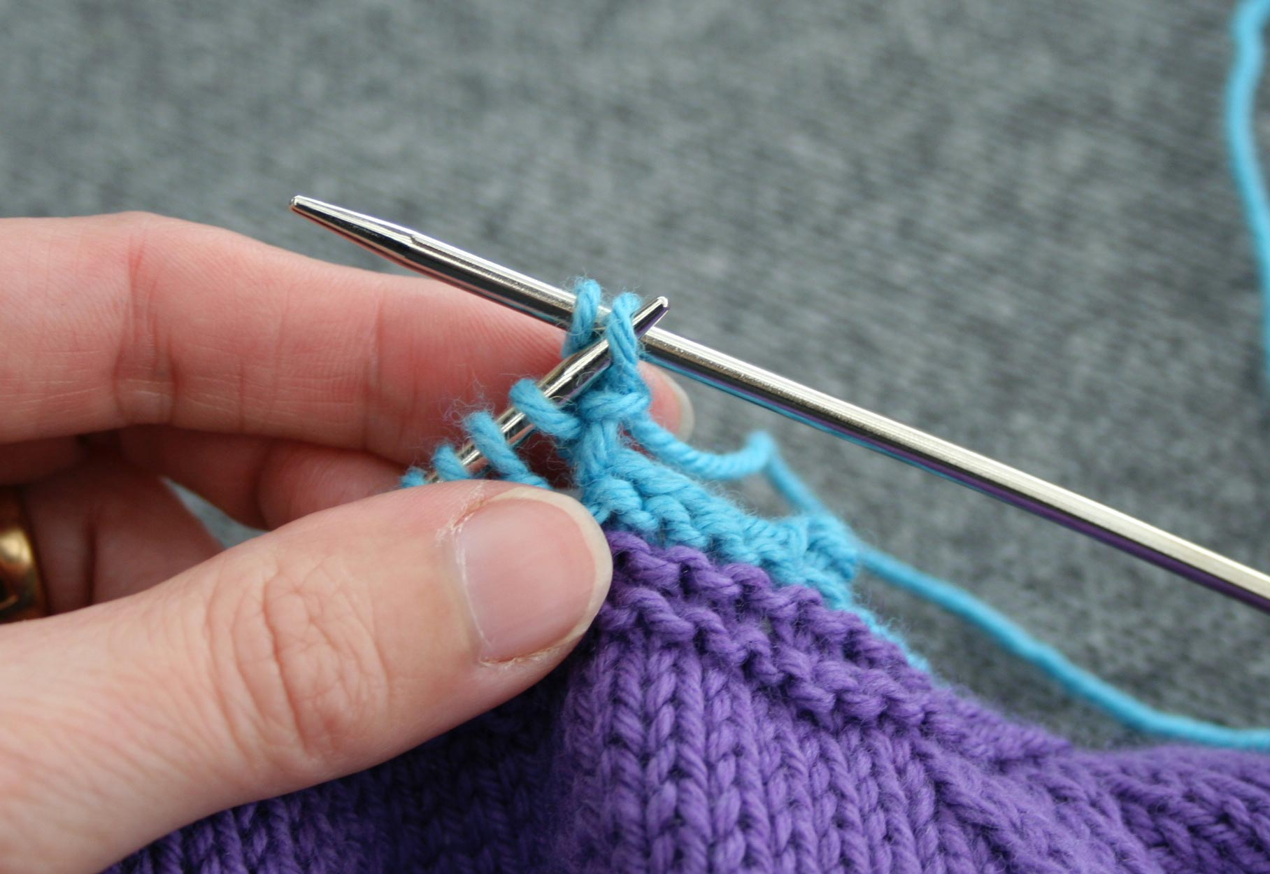 Left needle inserted in second stitch from end of right needle, preparing to pass it over last stitch worked.