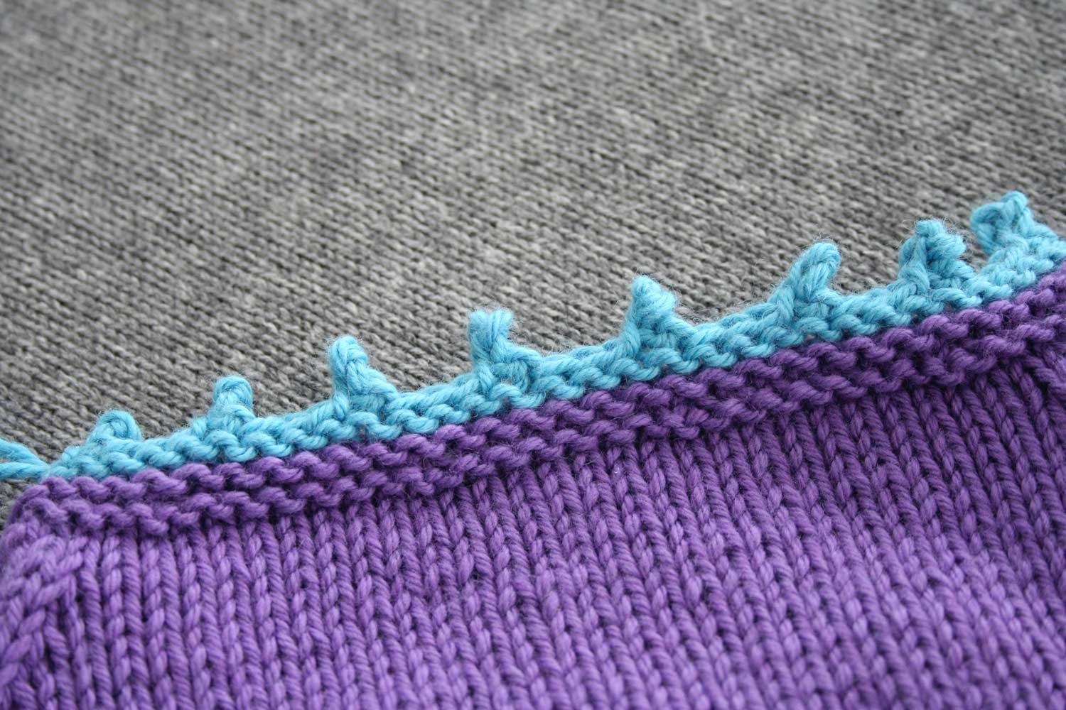 Back neck of purple sweater with contrasting blue completed picot bind off.