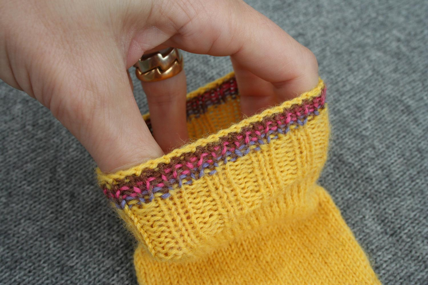 Hand stretching the opening of a sock showing how stretchy the bind off is.