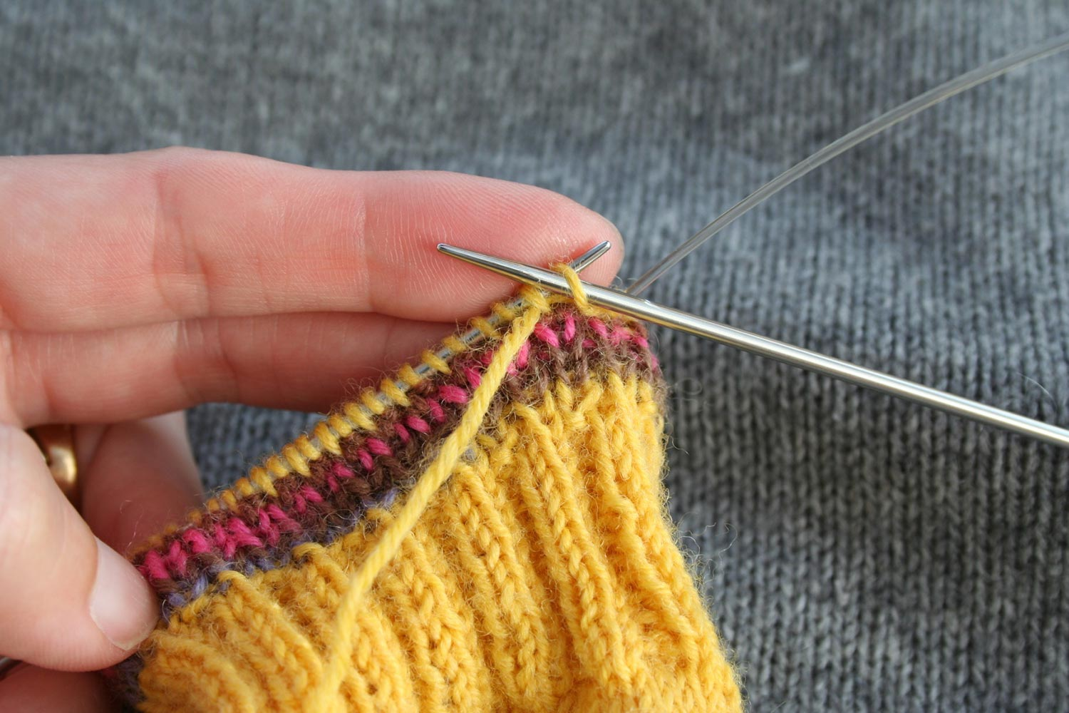 Right needle inserted purlwise through first stitch on left needle; working yarn is coming from the second stitch on the left needle.